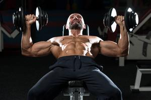 Man working out the upper chest muscles with incline dumbbell press