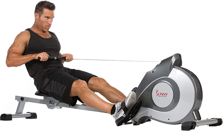 Man focused on rowing workout using magnetic machine