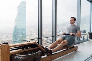 Man rowing on water rowing machine in skyscraper.