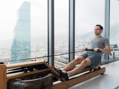 Man rowing on water rowing machine in skyscraper.