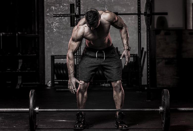 Strong bodybuilder picking up barbel
