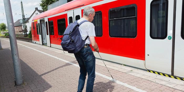 A blind person with a white cane on a train station. Photo