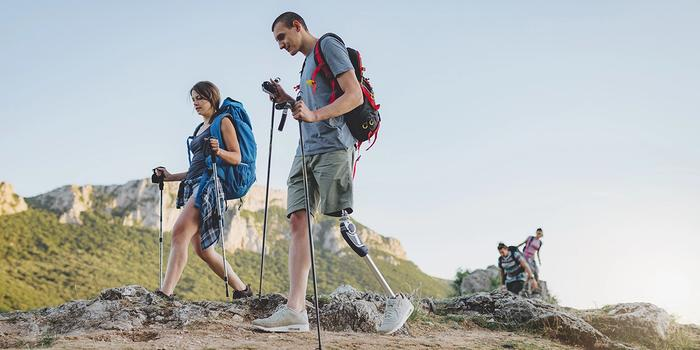 People who go hiking, including a person with a prosthesis. Photo
