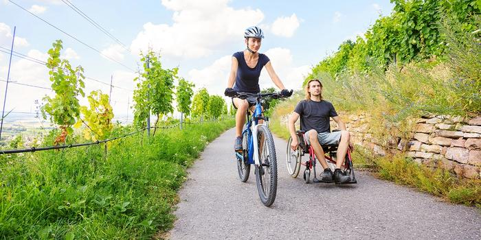 A person on a bike and a person in a wheelchair. Photo