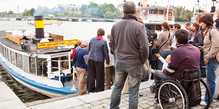 Tourists, one of whom is in a wheelchair who is about to board a boat. Photo