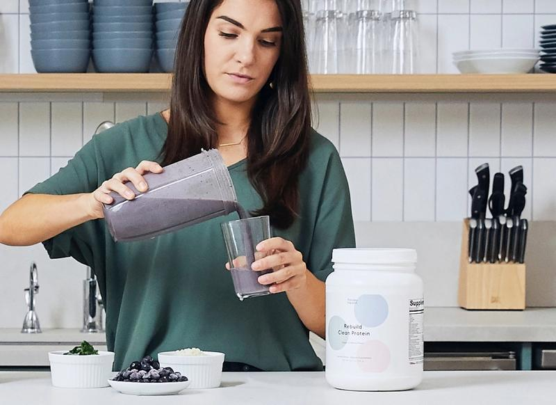 Woman pouring protein smoothie in a glass