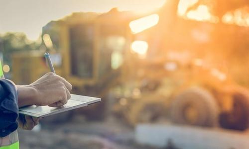 Bildet viser en ingeniør med tablett som gjør en inspeksjon på en byggeplass