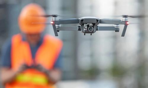 Bilder viser mann som styrer drone