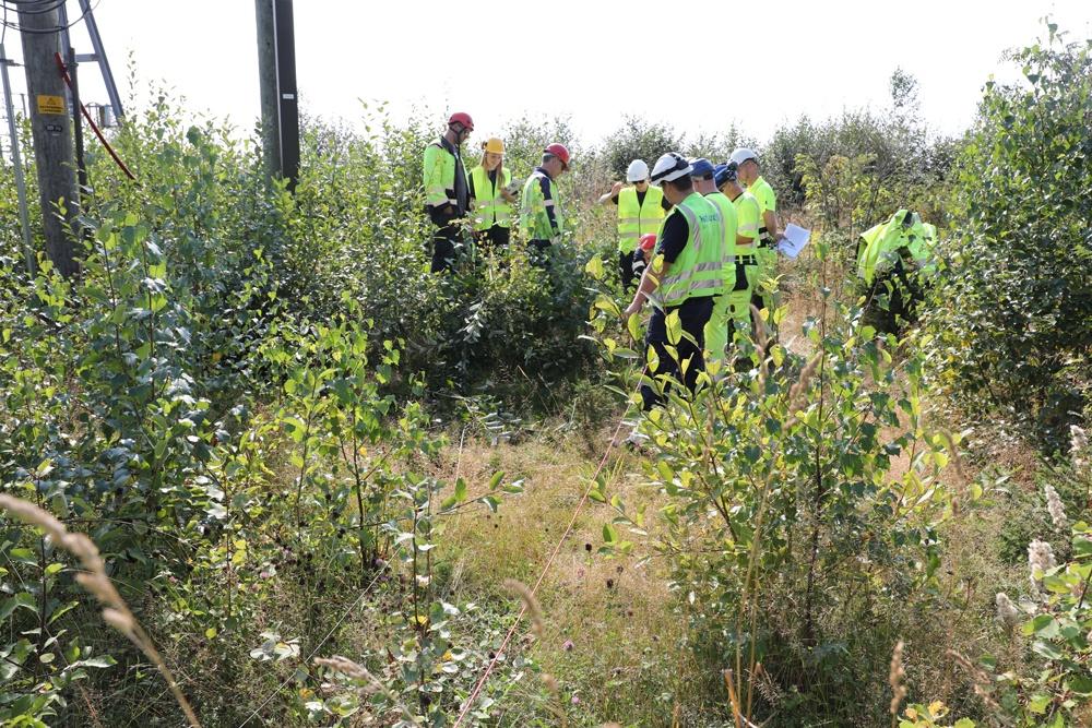 Bildet viser folk i refleksvest og hjelm i utmark. Praktisk demonstrasjon i feltet.