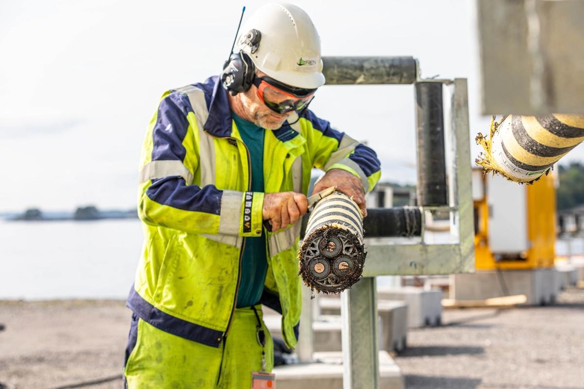Bilde viser mann som jobber med å kutte en sjøkabel