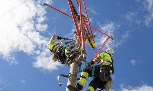Bildet viser to menn som klatrer i en strømstolpe