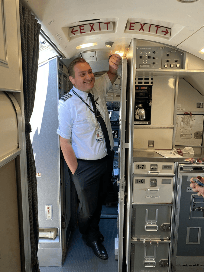 Pilot in aircraft galley smiling at something off camera.
