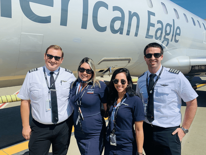 Pilots and flight attendants standing in front of an airplane.