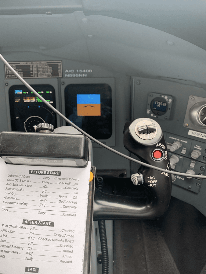 Paper checklist held in a clipboard on the control column of an aircraft.