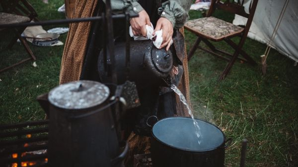 Person pouring boiling water from a kettle.