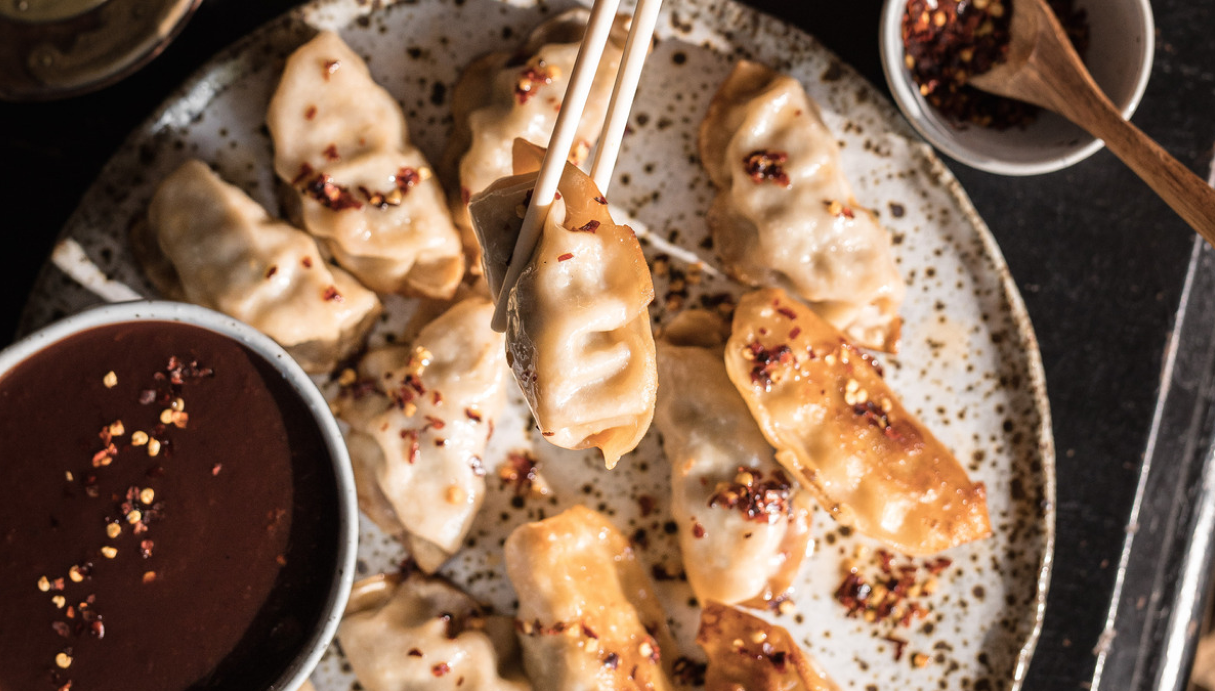 Dumplings being held by chopsticks, about to be dipped into plum sauce