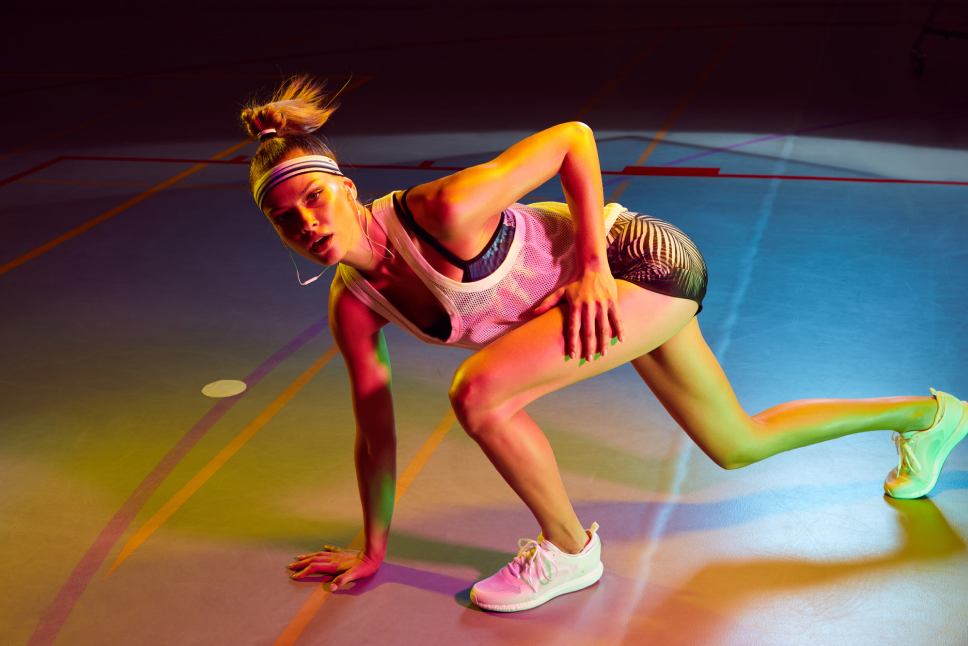 Woman in sportswear stretching under different coloured lights