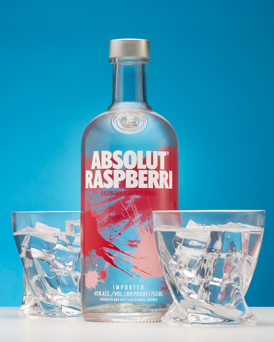 Bottle of Absolut Rasberri vodka with two glasses filled with vodka and ice