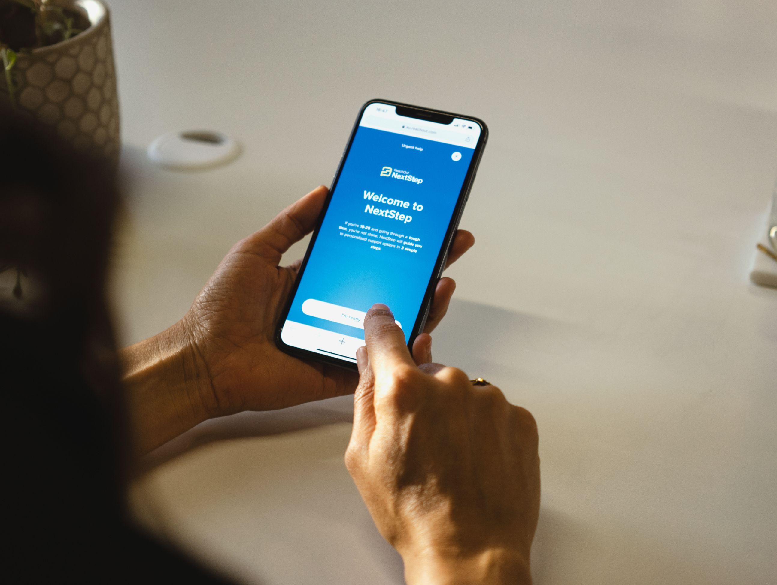 Holding phone ReachOut website