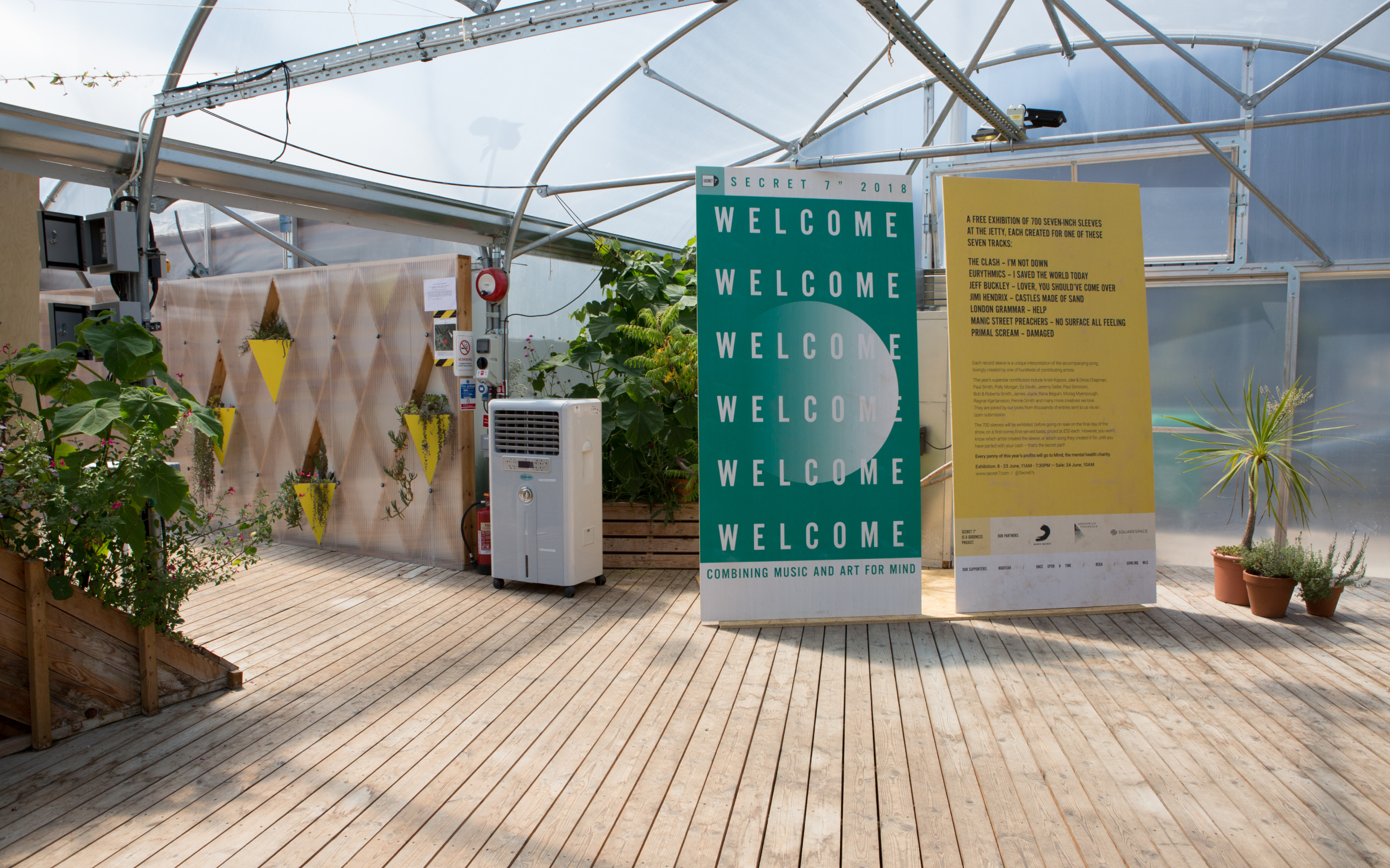 "The Secret7"" exhibition welcome banners in an outdoor area"
