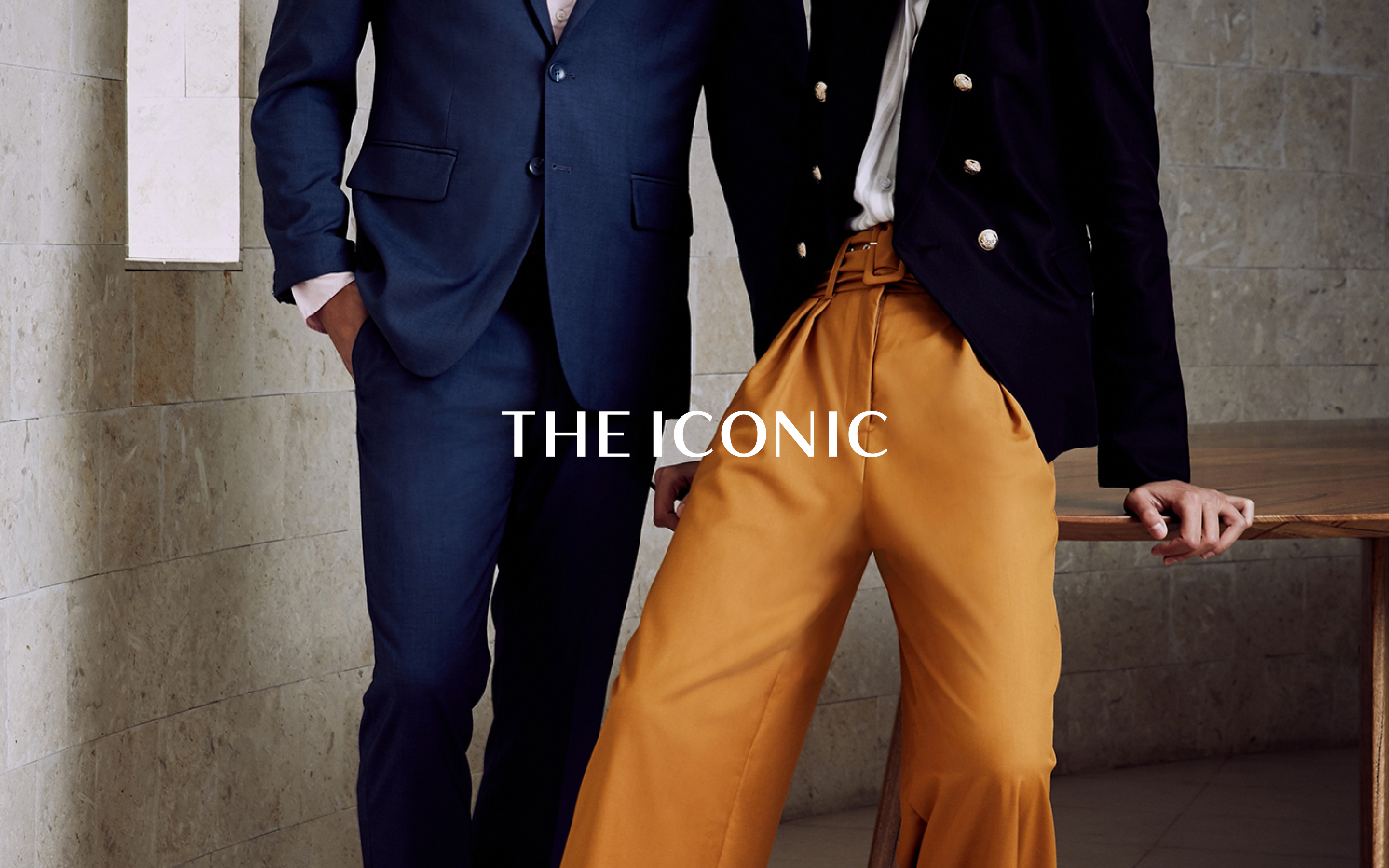 Two smartly dressed people modelling against a wooden table