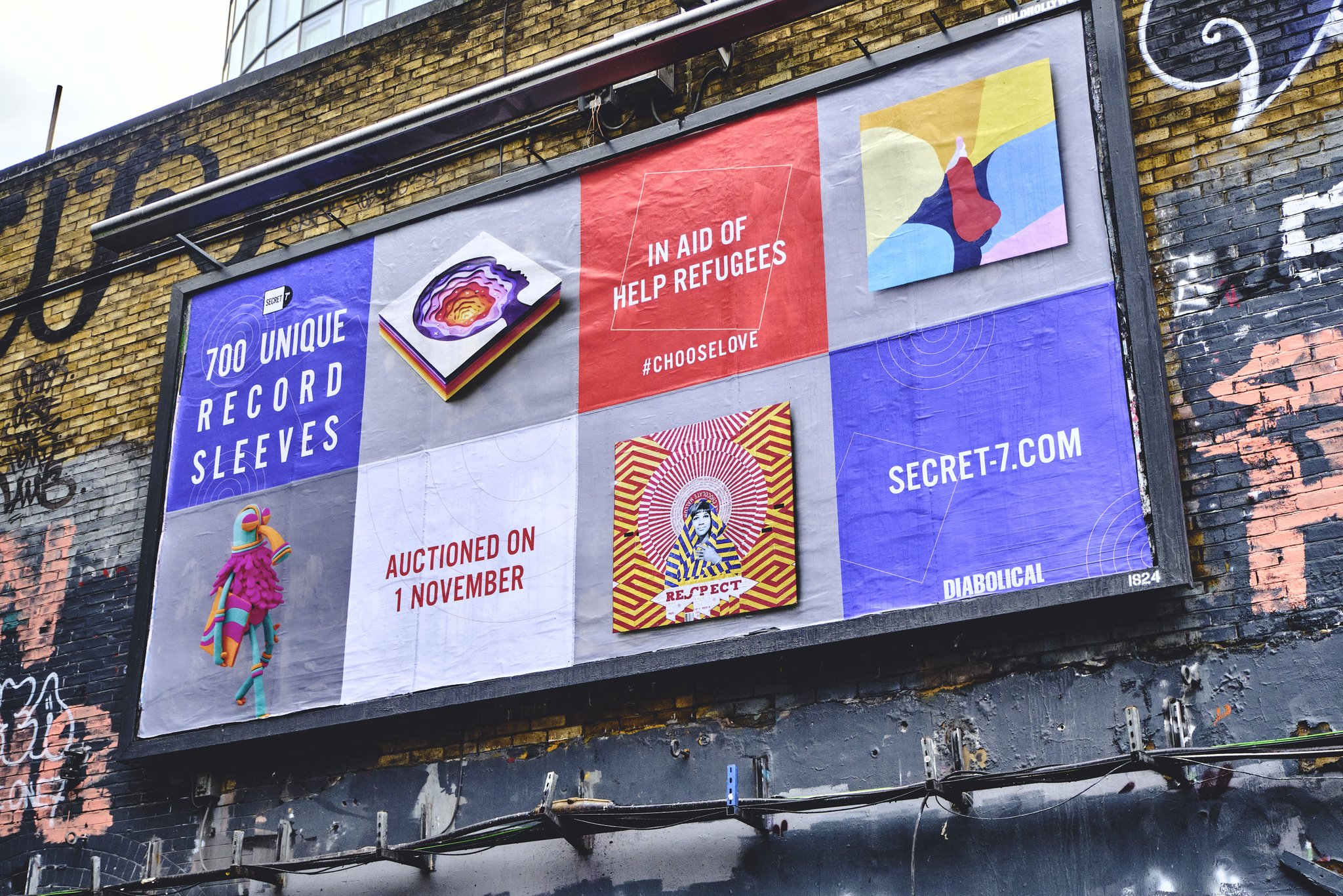 "Secret7"" billboard on a graffitied wall in london"