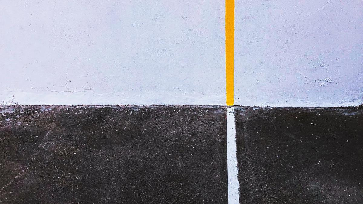 yellow line on wall meeting white line on black pavement