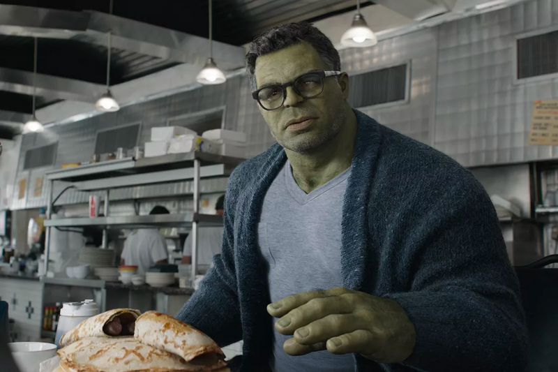 The Hulk (Bruce Banner) with glasses and a cardigan in front of pancakes