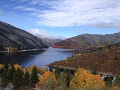 Ruedi reservoir in the fall with yellow aspen trees and a dusting of snow in the distant mountains with blue in the sky