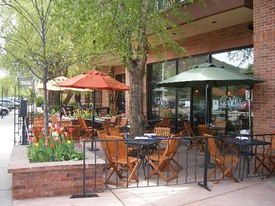 Outdoor dining patio with a brick planter out front with flowers with a small tree in the middle. An iron gated seating area with yellow, orange, and green umbrellas in Basalt, CO.