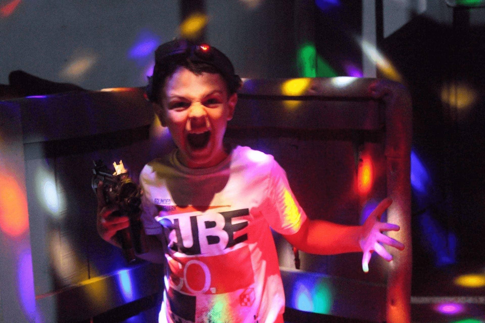 Возбужденный мальчишка воинственно рычит с лазертаг автоматом в руках