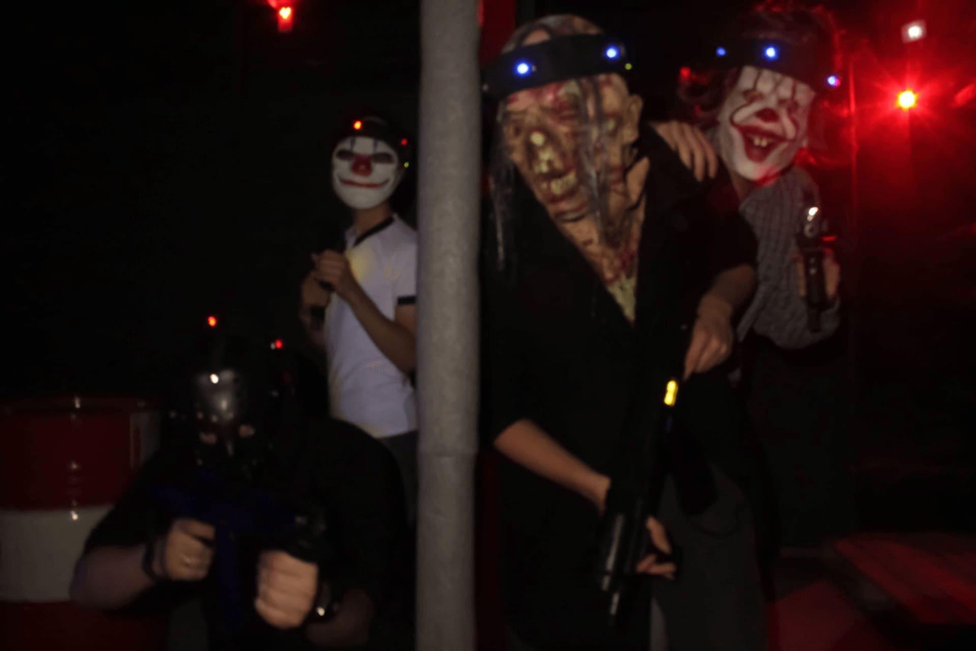 Люди в страшных клоунских масках выглядывают из тьмы