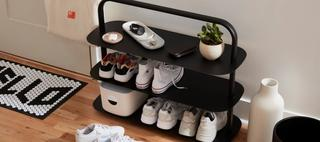 The black entryway rack with three shelved with shoes and bins.
