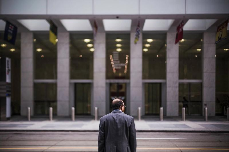 Man in a suit standing in front of a financial building