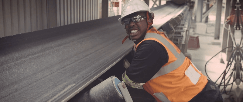 Anglo American employee in hard hat and high-vis jacket working with machinery