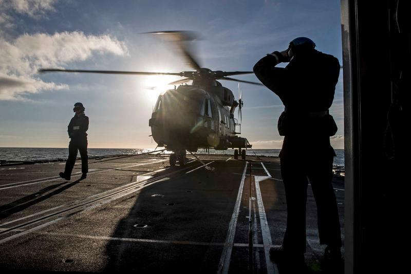 Two people from the RAF watching as helicopter lands
