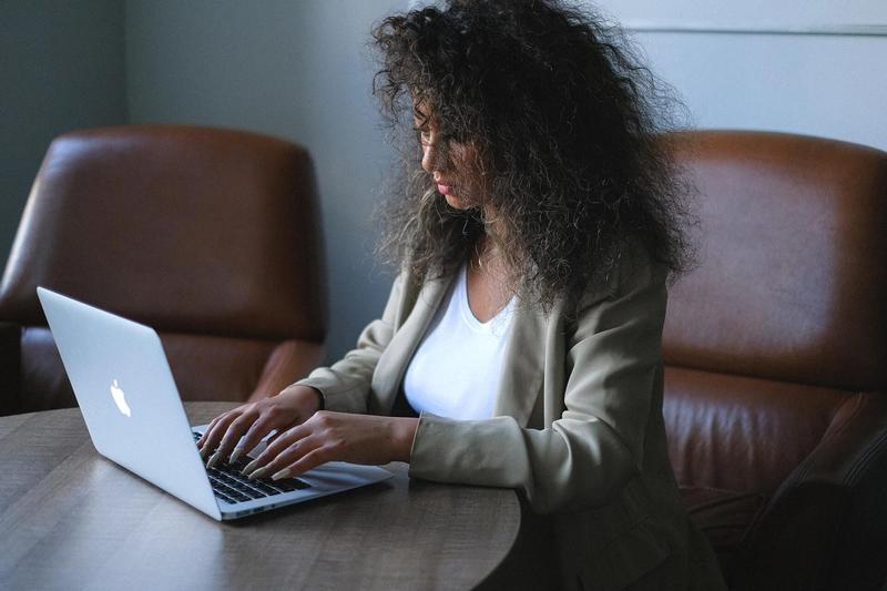 Female employee of financial services organization in a suit working on her laptop at a desk