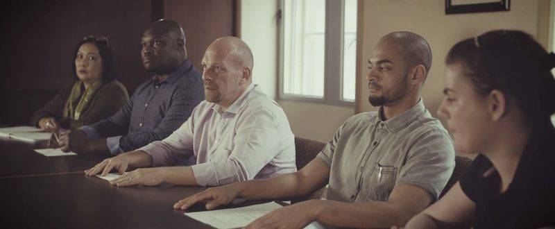 Five Anglo American employees sat in a row at a desk, undertaking health and safety training