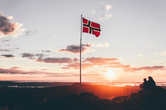 Norwegian flag on top of a mountain in the sun set