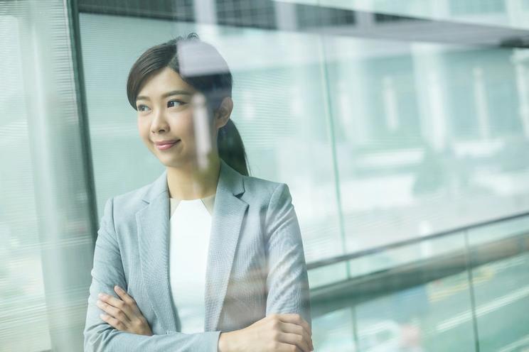 Business woman titter smilende ut av vindu