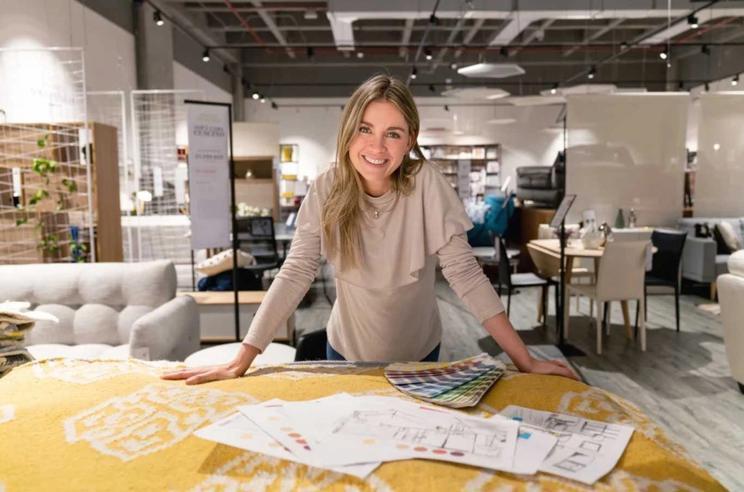 Kvinne i kontorlokale lener seg på et bord med diverse dokumenter spredd utover