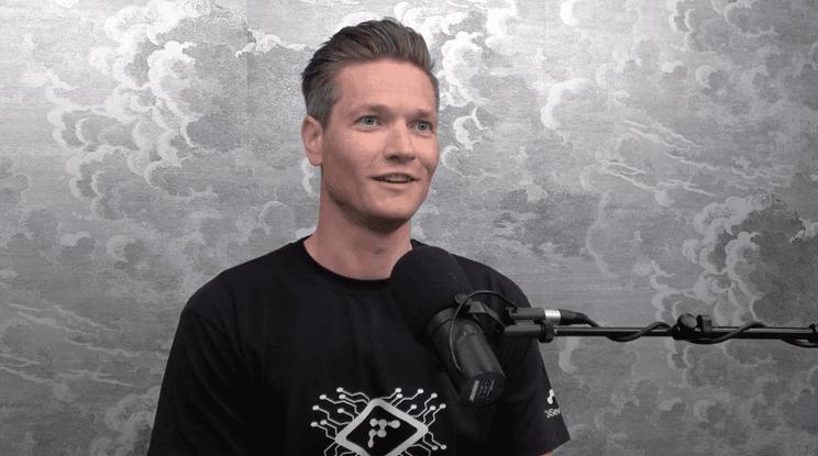 Mann i halvfigur foran mikrofon med grå vegg bak