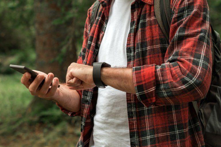 Mann som registrerer timer på nett ute i skogen