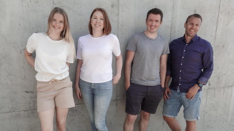 Fire personer i helfigur foran grå vegg
