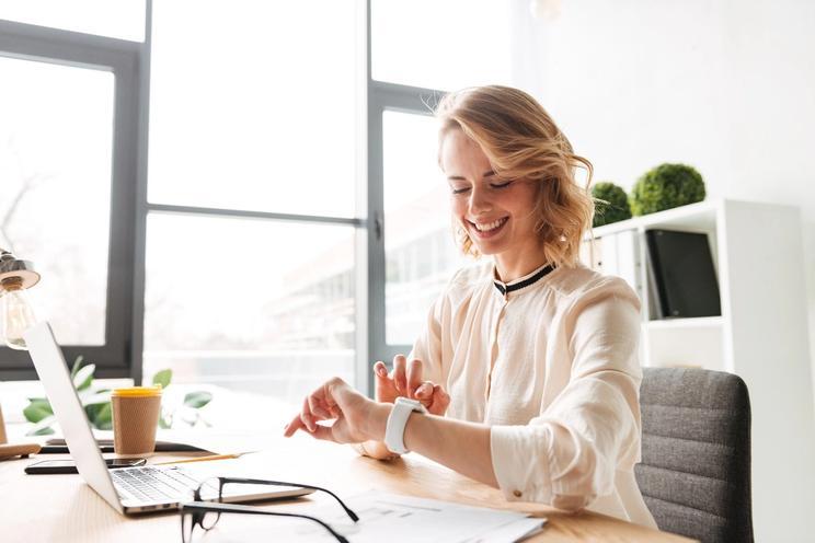Glad ung dame på kontoret ser på smartklokken sin