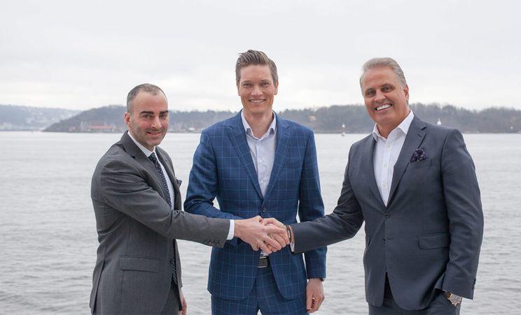 Tre menn står foran Oslo-fjorden og håndhilser for å bekrefte avtale