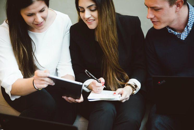 Tre kollegaer sitter i en sofa og ser sammen på en notatblogg