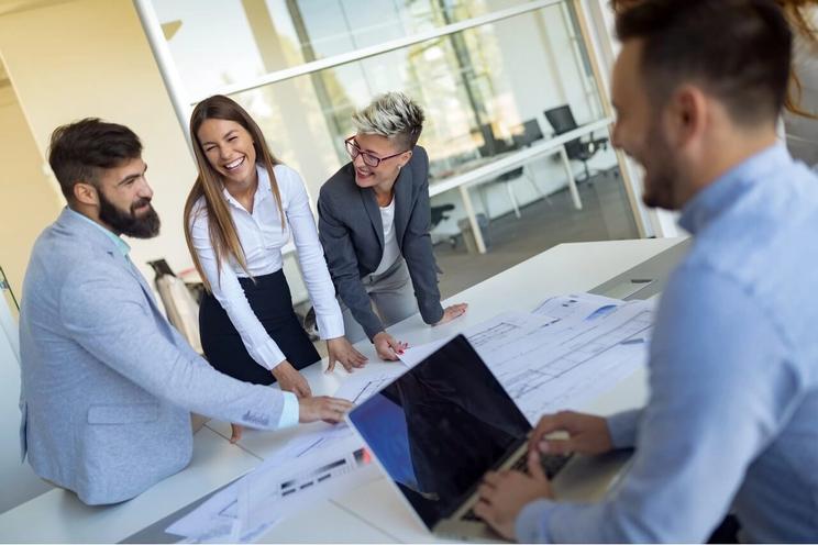 Glade kollegaer står ved et bord fullt av ark