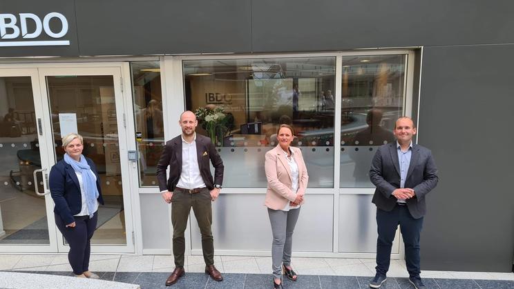 Fire mennesker foran inngangsparti på et kontorbygg