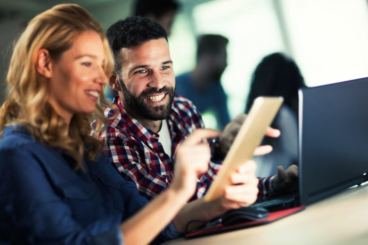 Smilende dame og mann samarbeider i et effektivt prosjektstyringsverktøy